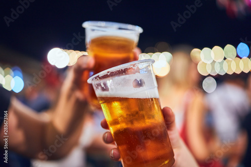 Friends drinking beer at night with de-focused lights in the background Fototapeta