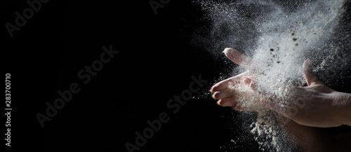 Fotografiet woman chef hand clap with splash of white flour and black background with copy space