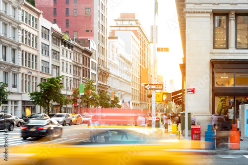 Foto New York City street scene with yellow taxi cab driving down 5th Avenue through