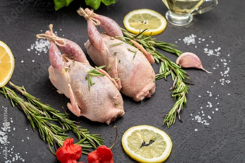 Wallpaper Mural Fresh raw meat quails with herbs and greens rosemary, basil ready for cooking on close-up