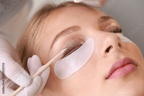 Obraz na płótnie Young woman undergoing procedure of eyelashes lamination in beauty salon, closeu
