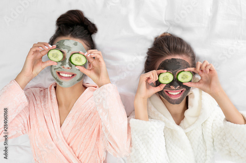 Fotografia Young friends with facial masks having fun on bed at pamper party, top view