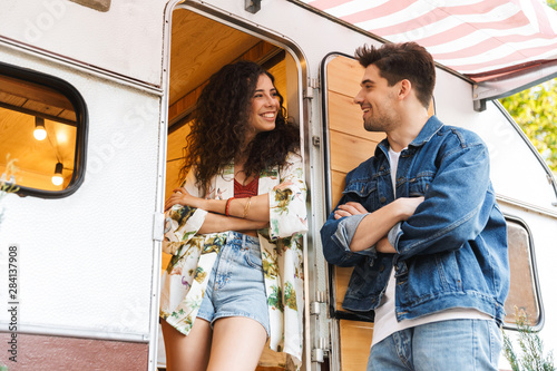 Fotografía Cheerful young couple talking while standing at the campvan