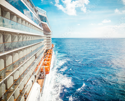 Billede på lærred Side view of cruise ship on the blue sky background with copy space, blue tone