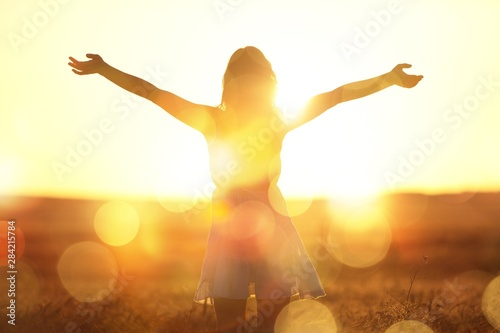 Fotografia, Obraz Young woman on field under sunset light