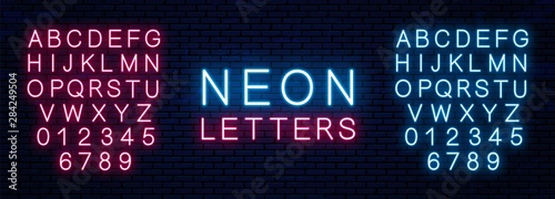 Obraz na plátně Bright neon letters of red and blue color isolated on brick wall background