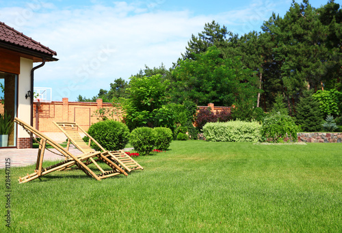 Wooden deck chairs in garden on sunny day