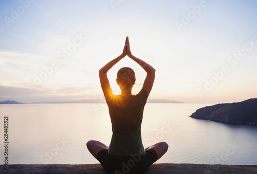 Young woman practicing yoga near the sea at sunset. Harmony, meditation, healthy lifestyle, relaxation, yoga, self care, mindfulness concept