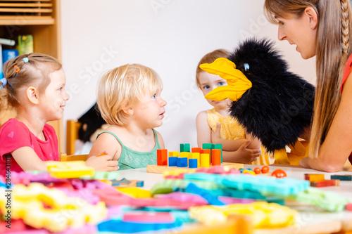Obraz na plátně Kindergarten teacher and children playing with hand puppet