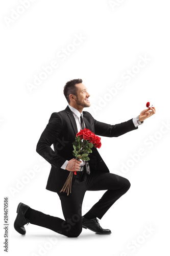 Young elegant man in a suit kneeling and holding roses and an engagement ring Fototapeta