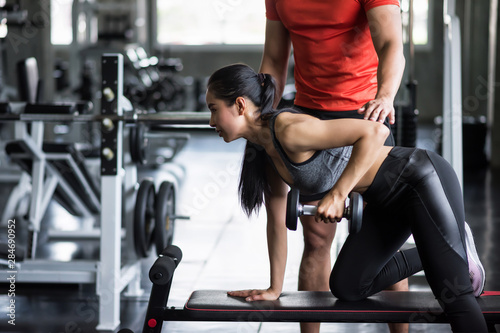 trainer coach dumbbell exercise to woman Fototapet