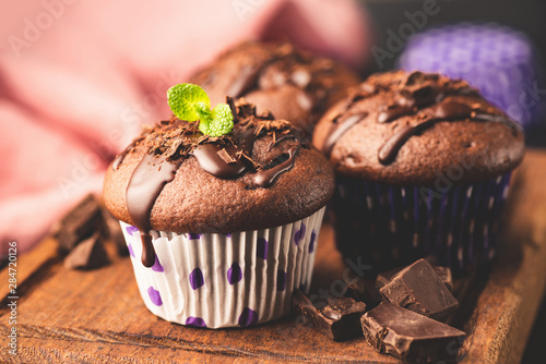 Fotografia Chocolate muffins decorated with chocolate sauce and mint leaf, served on wooden board