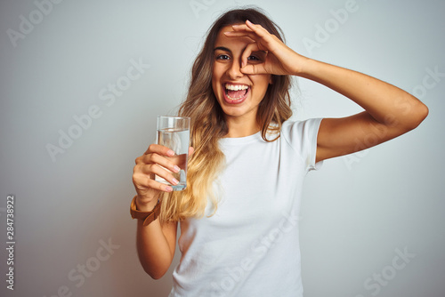 Valokuvatapetti Young beautiful woman drinking a glass of water over white isolated background w