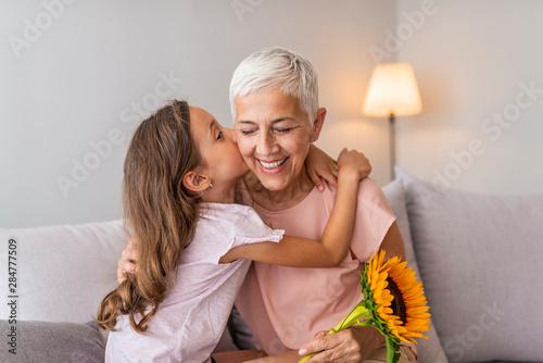 Fototapeta Happy senior grandma hugging granddaughter thanking for gift and flowers