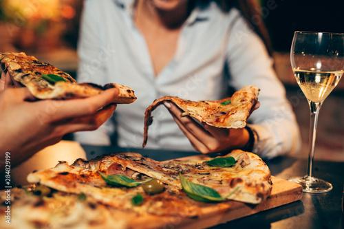 Stampa su Tela closeup of friends eating pizza
