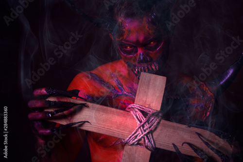 Photo Bad devil or monster bite the holy cross on halloween day