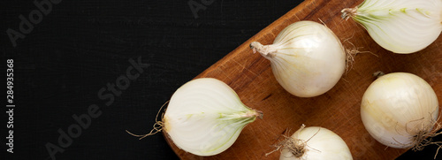 Fotografia Raw white onions on a rustic board on a black background, overhead view