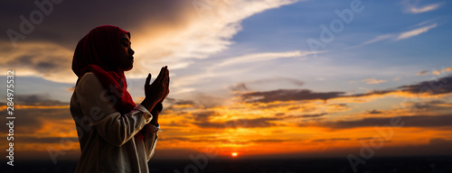 Fotografia Silhoueitte of young muslim woman pray with beautiful sunset/ sunrise in backgro