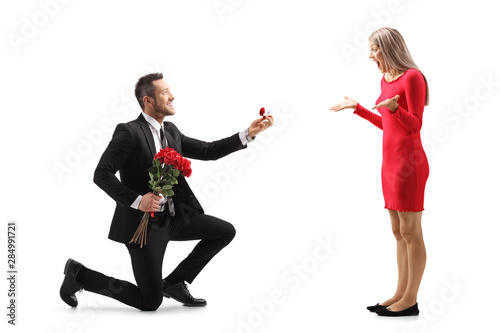 Fototapeta Young man kneeling with roses and an engagement ring and proposing to a surprise
