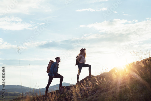 Fotografie, Obraz Young tourist couple travellers with backpacks hiking in nature.