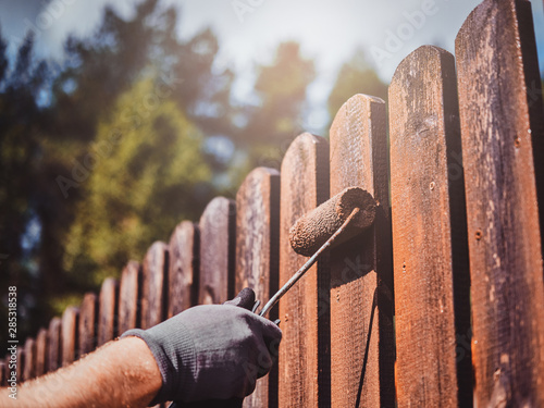 Fotografie, Tablou Man in protective gloves is painting wooden fence in bright summer day