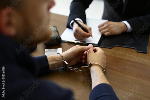 Slika na platnu Police officer interrogating criminal in handcuffs at desk indoors