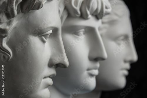 Gypsum copy of ancient statue Apollo, Antinous and Venus head on dark textured background Fototapete