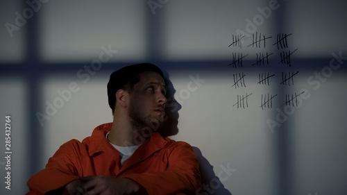 Billede på lærred Male prisoner looking at crossed lines on cell wall, serving long imprisonment