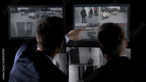 Fotografia Private agents monitoring CCTV footage, searching for criminal, discussion