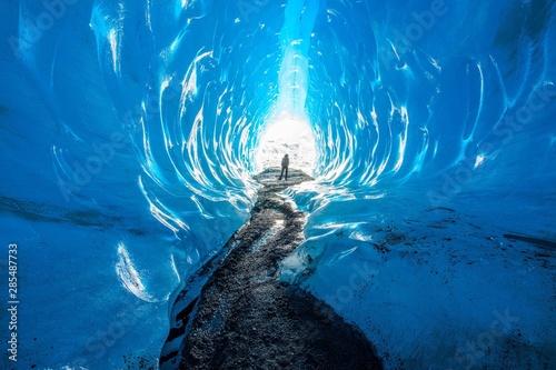 Fototapeta A woman silhouette outside an ice cave in Alaska