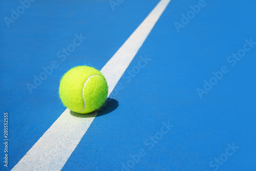 Photo Summer sport concept with tennis ball on white line on hard tennis court blue color