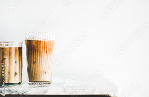 Fotografia Homemade iced latte coffee in glasses with straws on marble table, white wall at background, copy space, close-up
