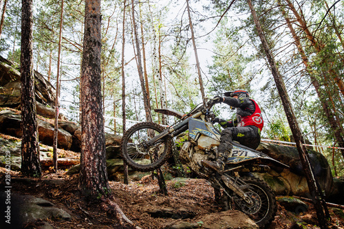 Photo athlete racer motocross enduro riding uphill in forest trail