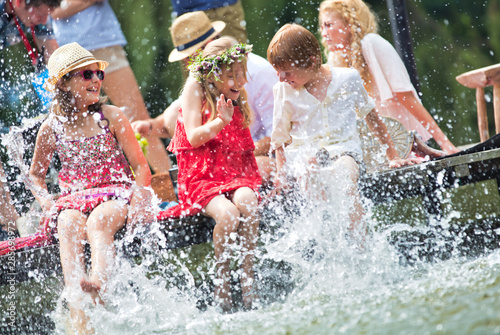 Canvas Print Photo of mother playing water with kids in lake while sitting on pier against fa