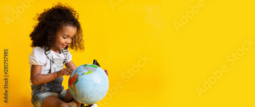 Photographie Early education. Little girl pointing to world globe