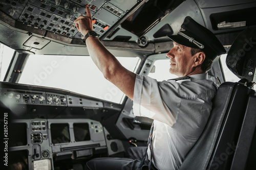 Concentrated pilot in cockpit looking at control panel Fototapeta