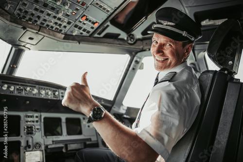 Fotografija Smiling pilot in cockpit looking at camera
