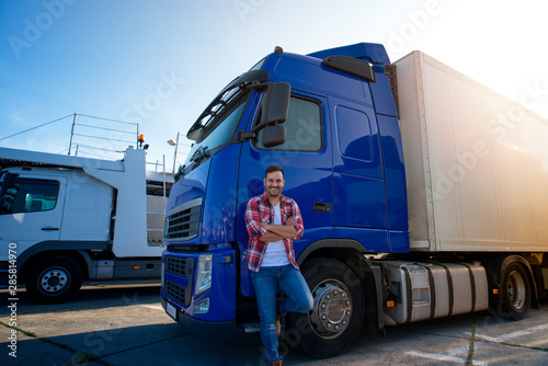 Obraz na plátně Truck driver with crossed arms and smile on his face standing by his truck on a break ready for a ride