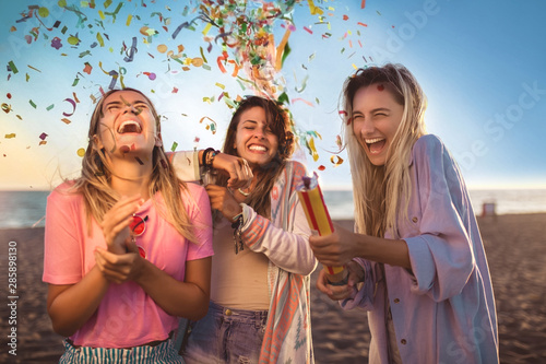 Billede på lærred Happy young people having fun at beach party, celebrating with confetti