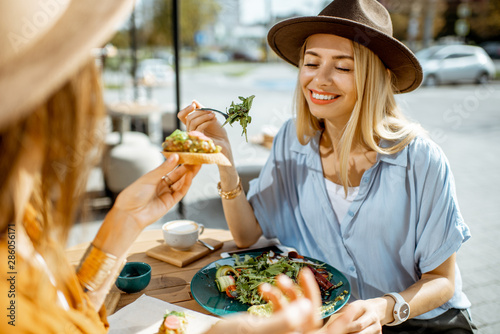 Canvas Print Two female best friends eating healthy food while sitting together on a restaura