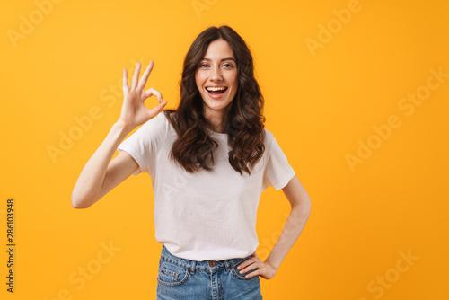 Valokuvatapetti Image of amazed brunette woman wearing casual clothes smiling and showing ok sig