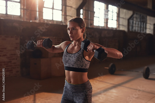 Fototapeta Sport woman doing fitness exercise with dumbbells at gym