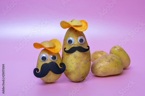 фотография funny potato head with face on pink background