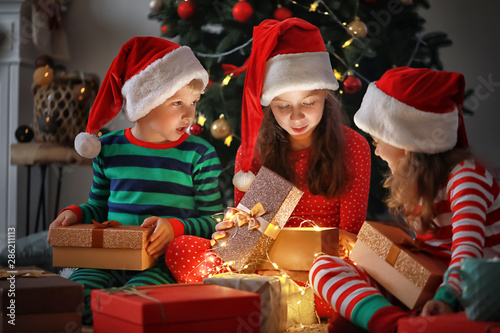 Stampa su Tela Cute little children opening magic Christmas gift at home