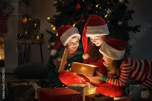 Fotografia Cute little children opening magic Christmas gift at home