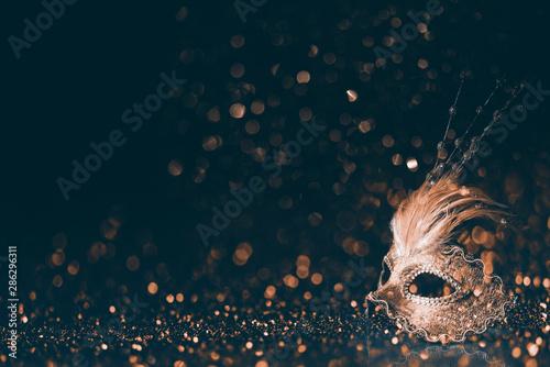 Leinwand Poster Luxury venetian mask on dark godlen bokeh background
