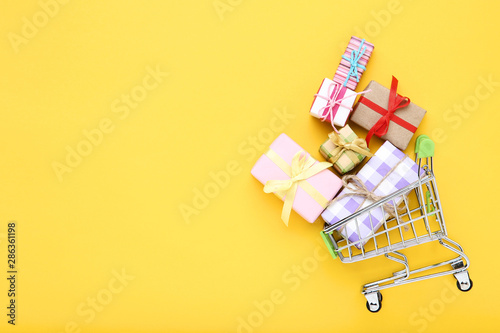 Fotografia, Obraz Small shopping cart with gift boxes on yellow background