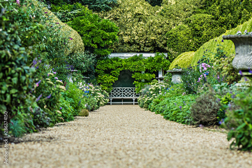 Fotografija Traditional landscaped English garden path with lush flowering bushes