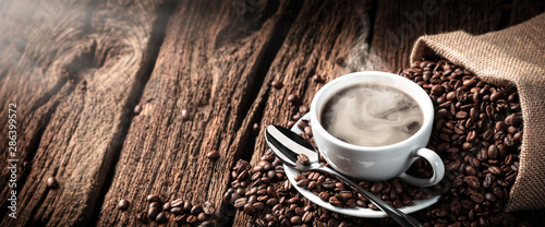 Fotografia White Cup Of Hot Steamy Coffee On Old Weathered Table With Burlap Sack And Beans