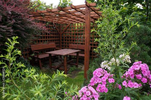 Fototapeta Drewniana altana ogrodowa w otoczeniu roślin i kwiatów